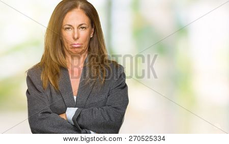 Middle age adult woman wearing oversize boyfriend jacket over isolated background skeptic and nervous, disapproving expression on face with crossed arms. Negative person. poster