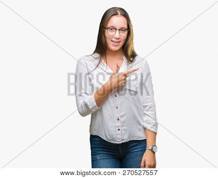 Young caucasian beautiful business woman wearing glasses over isolated background cheerful with a smile of face pointing with hand and finger up to the side with happy and natural expression on face