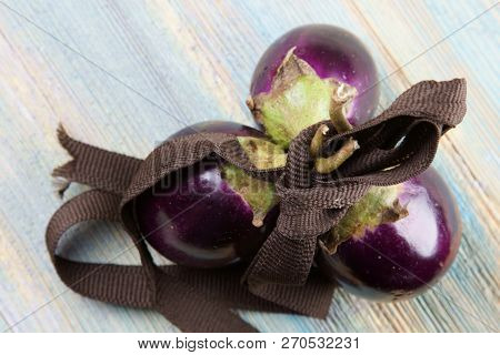 Small Purple Eggplants On A Wooden Background.
