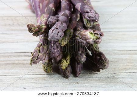 Purple Asparagus In A Bunch On A Wooden Background.