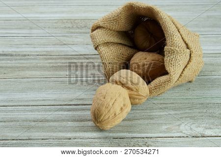 Walnuts In A Burlap Bag With Copy Space On A Wooden Background.