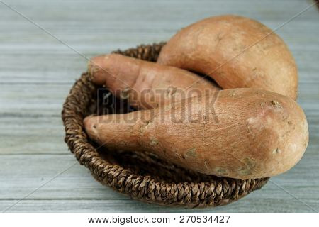 A Basket Of Sweet Potatoes On A Wooden Background.