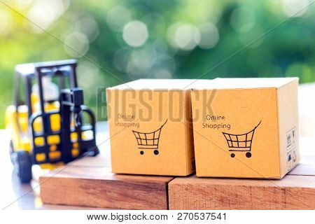 Cardboard Boxes With Shopping Cart Symbol On Wooden Block And Mini Crane Truck Nearby With Natural B