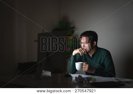 Attractive Young Asian Man Drinking Coffee Sitting On Desk Table Looking At Laptop Computer In Dark