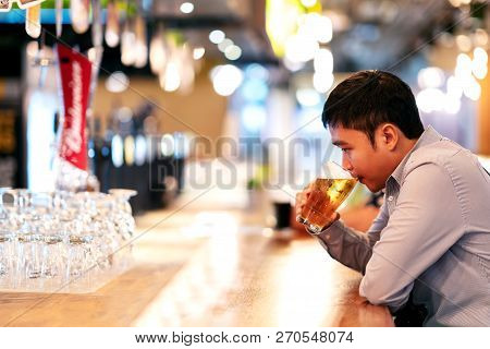 Young Asian Business Man Or Freelancer Sitting At Night Club Bar Drinking Beer Feeling Thoughtful. A