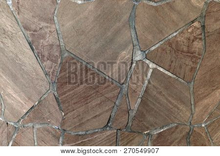 Natural Stone Of Brown Color, A Piece Of A Wall From A Natural Stone. Background Of Natural Stone.st