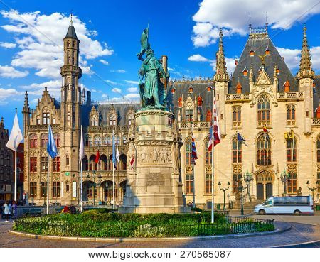 Bruges, Belgium. Central market square Grote Markt, historical centre with building of Provincial government and monument in honor of Jan Breydel Pieter De Coninck morning panorama with blue sky.