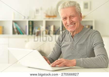 Portrait Of Happy Senior Man Using Laptop