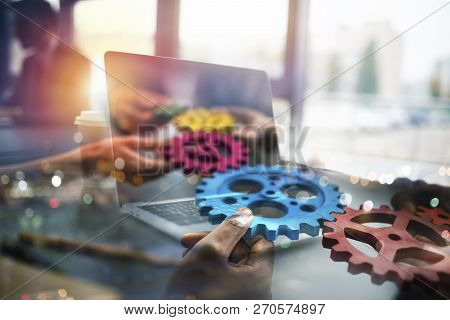 Business People With Gears In Hand That Exit From A Laptop. Concept Of Remote Cooperation And Teamwo