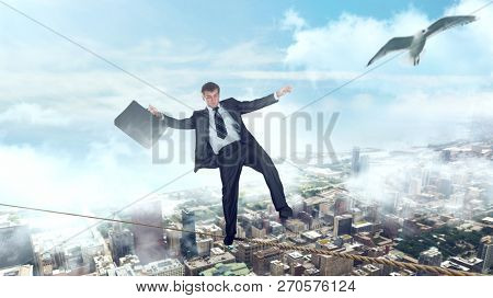 Businessman walking on a rope over business center