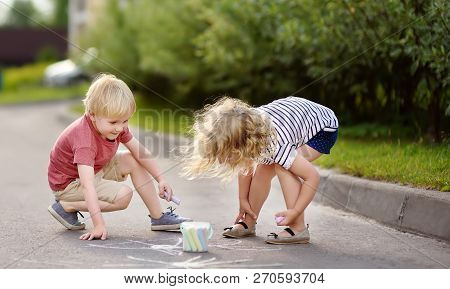Happy Little Boy And Girl Drawing With Colored Chalk On Asphalt. Creative Leisure For Toddler Child.