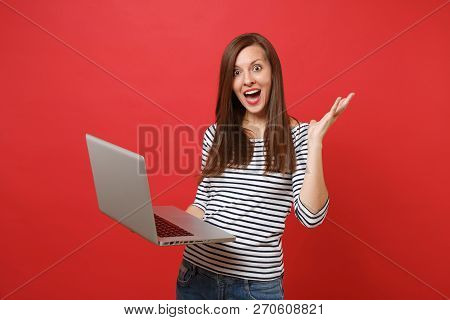 Excited Young Woman Keeping Mouth Wide Open, Looking Surprised, Spreading Hands Working On Laptop Pc