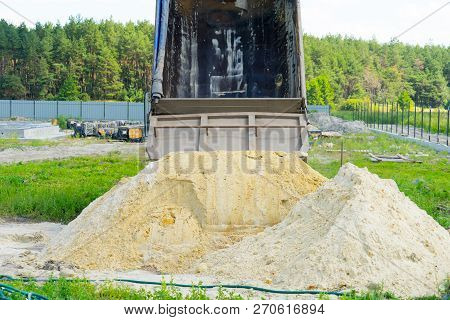 Delivery Of Sand For Construction. Dump Truck Unloads The Sand. Place For Your Text.