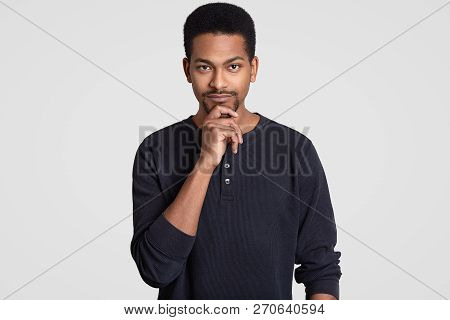 Shot Of Serious Male Entrepreneur Holds Chin, Has Afro Hairstyle And Dark Skin, Looks Seriously At C