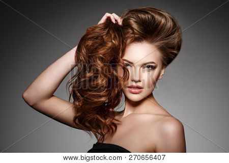 Beauty Fashion Model with long shiny  hair. Waves & Curls volume Hairstyle. Hair Salon. Updo. Woman with healthy hair girl with luxurious Updo haircut. Hair loss.