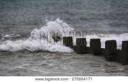 Sea Splashing Against A Groyne On A Beach