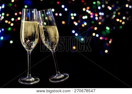 Two Champagne Glasses Toast Against A Dark Background With Colorful Bokeh Lights, New Year And Party