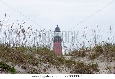 A Lighthouse As Seen From The Beach.