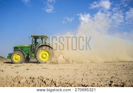 Badajoz, Spain - Oct 11th 2017: Farm Tractor Preparing Dusty Soil Affected By Drought. Drought And A