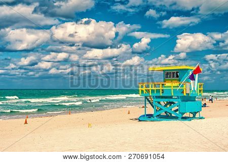 South Beach, Miami, Florida, Lifeguard House In A Colorful Art Deco Style Blue And Yellow On Cloudy
