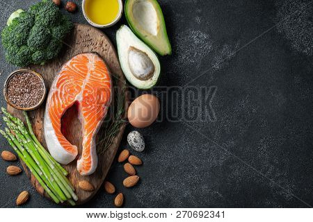 A Set Of Healthy Food For Keto Diet On A Dark Background. Fresh Raw Salmon Steak With Flax Seeds, Br