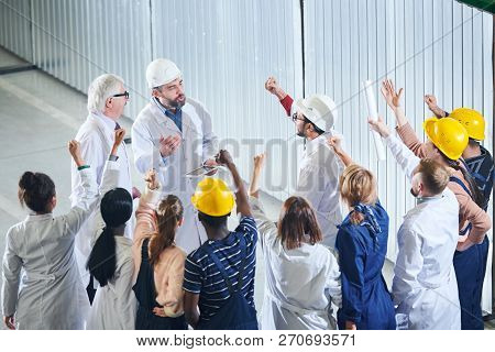 High Angle Portrait Of Mature Factory Managers Talking To Group Of Emotional Workers During Meeting