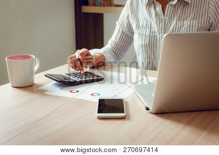 Close Up Portrait Of Businesswoman Accountant Using Calculator And Laptop For Matching Financial Dat