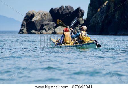 Brookes Peninsula, Vancouver Island, Bc, July17, 2018: Two People Wearing Life Jackets Paddle A Kaya