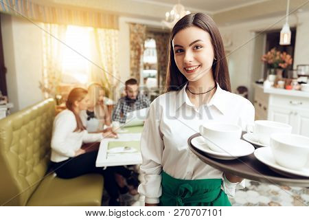 Portrait Smiling Young Waitress Standing In Cafe. The Happy Girl The Waiter Holds In Bunches A Tray