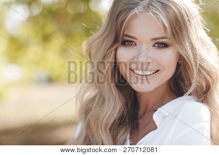 Portrait Of A Beautiful Woman With Curly Hair Outdoors In A Spring Park.portrait Dreamy And Air Attr