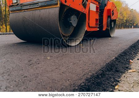 Workers Operating Asphalt Paver Machine During Road Construction. Close View On The Road Roller Work