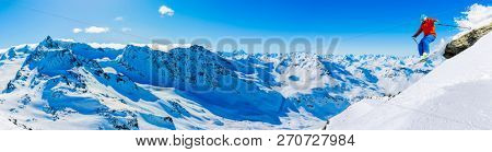Ski in winter season, mountains and ski jumping man on the top in sunny day in France, Alps above the clouds.