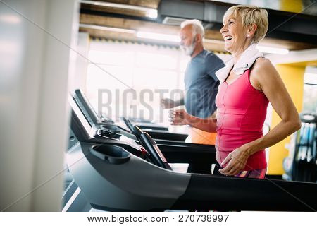 Senior People Running In Machine Treadmill At Fitness Gym Club