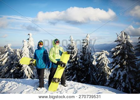 Two Snowboarders Posing At Ski Resort. Riders Friends Carrying Their Snowboards Through Forest For B