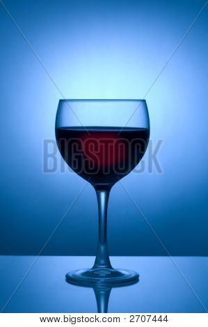 Glass Of Wine Silhouetted Against Blue Spotlight