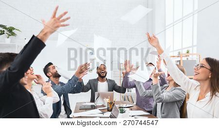 Successful Group Of Business People Celebrating Success Throwing Paper In Office