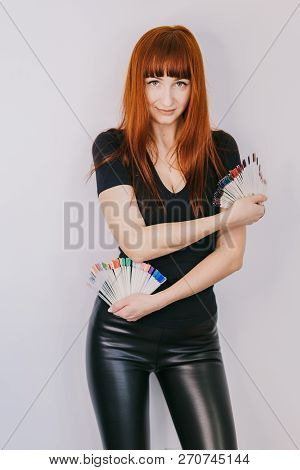 red-haired girl stands with samples of gel-lacquer in the studio. Manicurist in black clothes shows samples of coloured varnishes poster