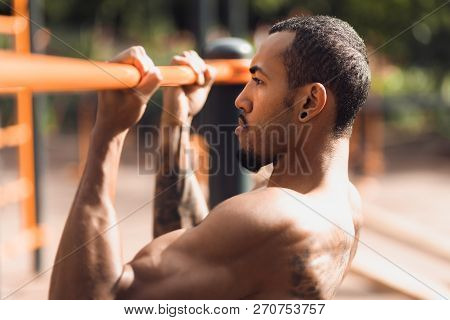 Crossfit Man Doing Pull-ups On Chin-up Bar During Workout Outdoors