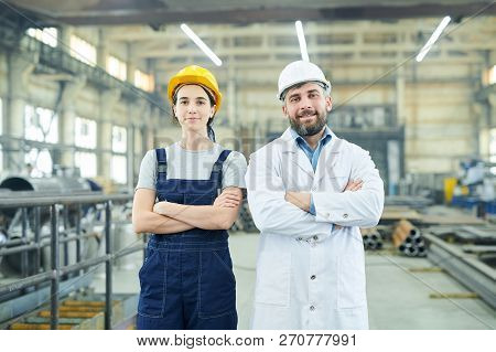 Waist Up Portrait Of Two Modern Factory Workers Looking At Camera While Posing In Industrial Worksho