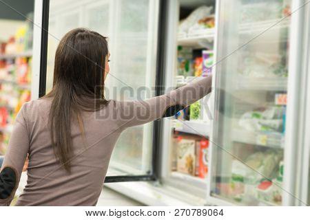 Woman taking deep frozen food from a freezer in a supermarket