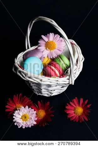 Sweet and colourful french macaroons in the basket on black background.