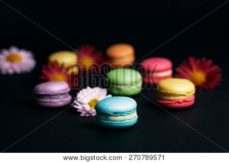 Sweet and colourful french macaroons on black background.