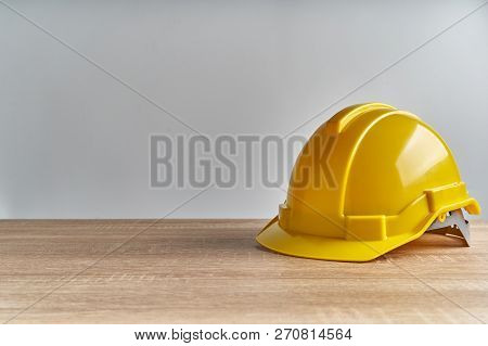 Yellow Engineer Hat Place On Wooden Table And Copy Space