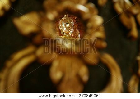 Closed Up The Face Of Golden Buddha Image Reflecting On The Mirror Of Teak Lacquered Pillar In Wat P