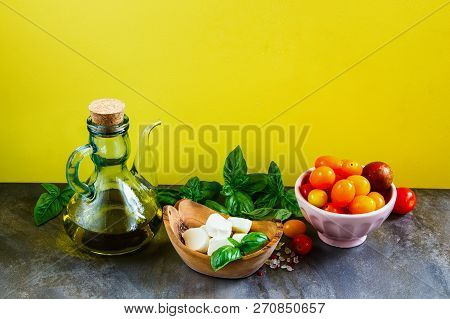 Tomato Mozzarella Basil Leaves And Olive Oil On Yellow Background. Italian Salad. Mediterranean Sala