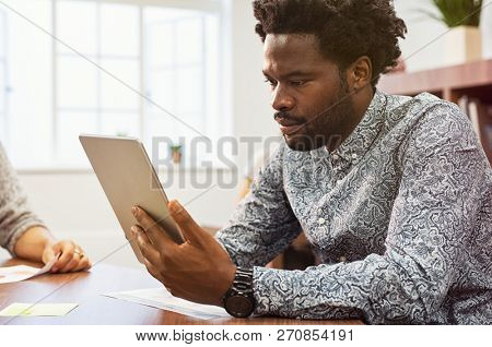 African american entrepreneur using digital tablet in his studio. Concentrated businessman working on digital tablet in a creative agency. Black casual man checking email on laptop sitting at desk.