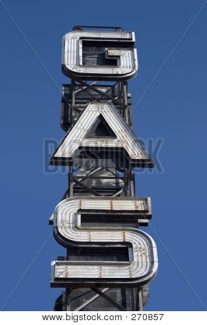 an industrial looking sign for a gas station against the blue sky. poster