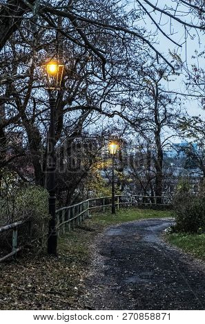 Evening Street Scene, Nitra, Slovak Republic. Lantern, Railing And Trees.