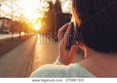 Woman Talking On Mobile Phone On Street In Sunset, Rear View Of Adult Caucasian Female Person Holdin