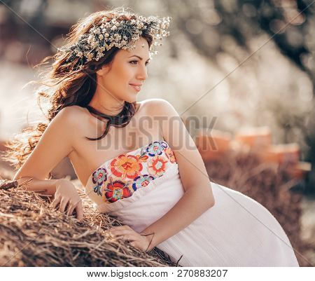 Portrait of beautiful young woman with makeup in chaplet from flowers poster